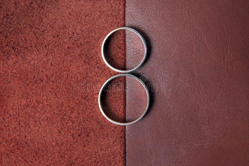 Обручальные кольца на коричневой кожаной предпосылке ткани стоковые изображения