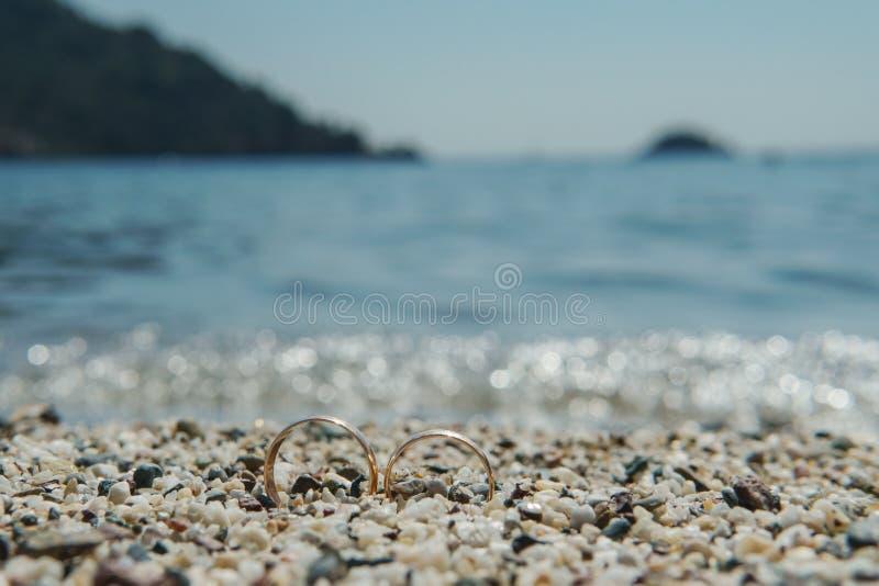 Обручальные кольца на пляже на море предпосылки голубом, стоковые изображения rf