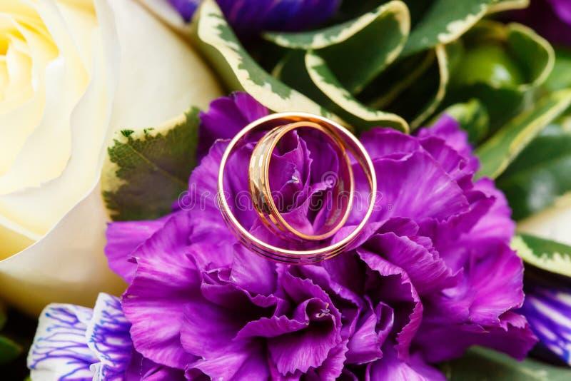 Обручальные кольца на bridal букете цветков стоковое фото