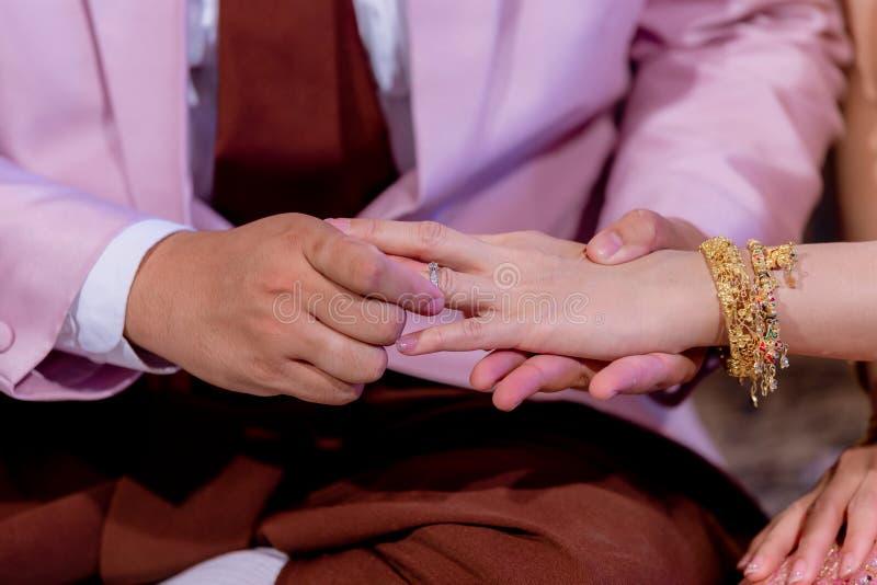 Обручальные кольца Он положил обручальное кольцо на ее Близко вверх выхольте для установки кольца на невесту стоковые фотографии rf