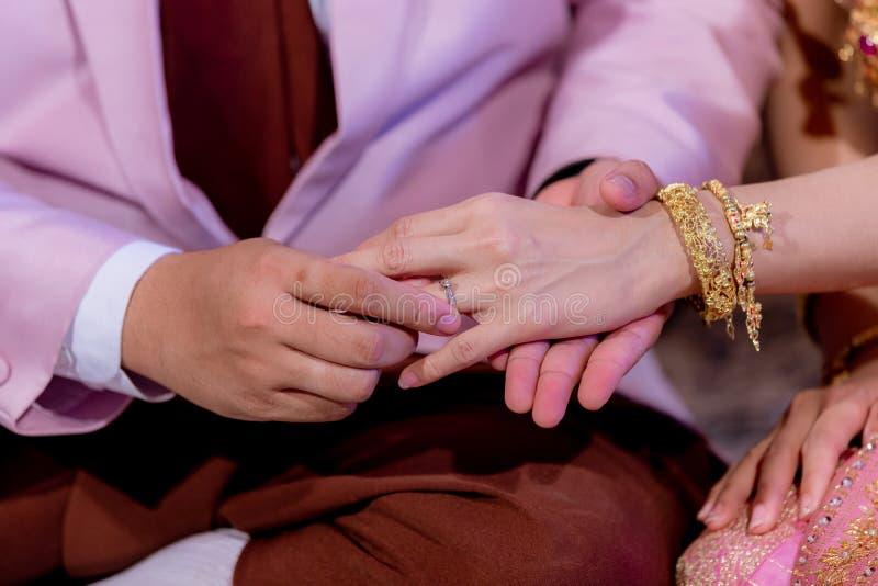 Обручальные кольца Он положил обручальное кольцо на ее Близко вверх выхольте для установки кольца на невесту стоковая фотография