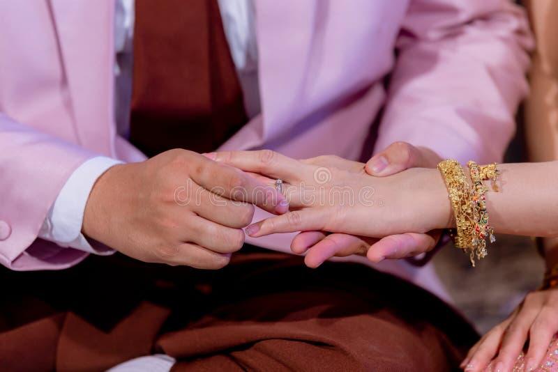 Обручальные кольца Он положил обручальное кольцо на ее Близко вверх выхольте для установки кольца на невесту стоковая фотография rf