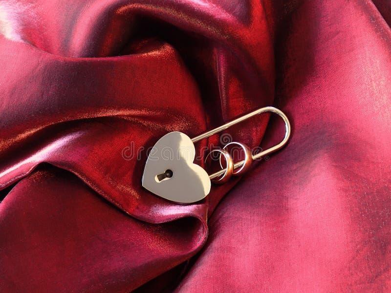 Обручальные кольца в замке на красной ткани стоковые фотографии rf