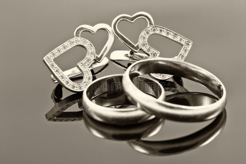 Обручальные кольца и серьги золота стоковая фотография rf