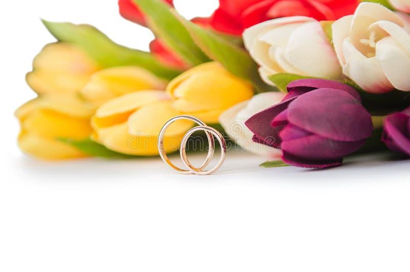 Обручальные кольца и цветки изолированные на белой предпосылке стоковые фото