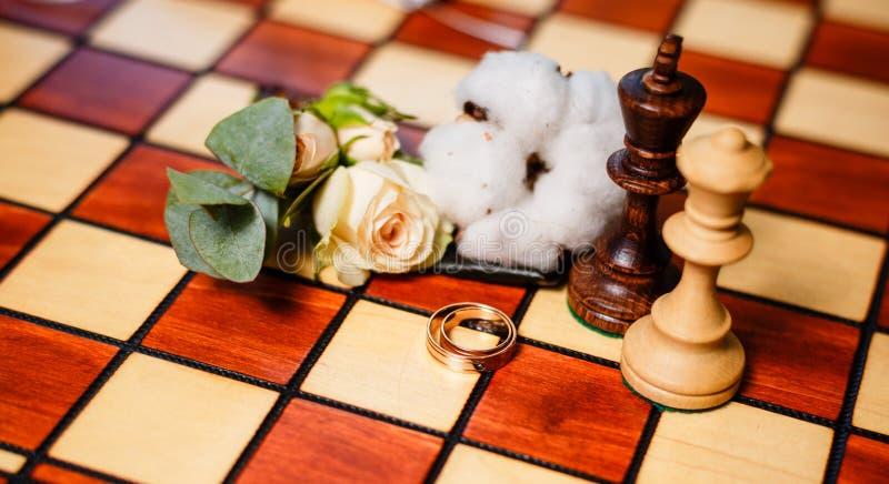 Обручальные кольца и шахмат стоковое фото
