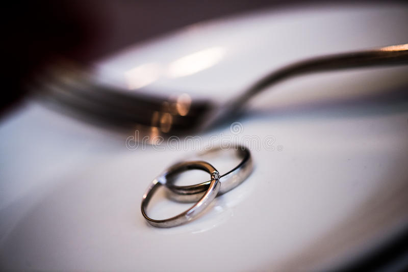 Обручальные кольца на плите с вилкой стоковые фото