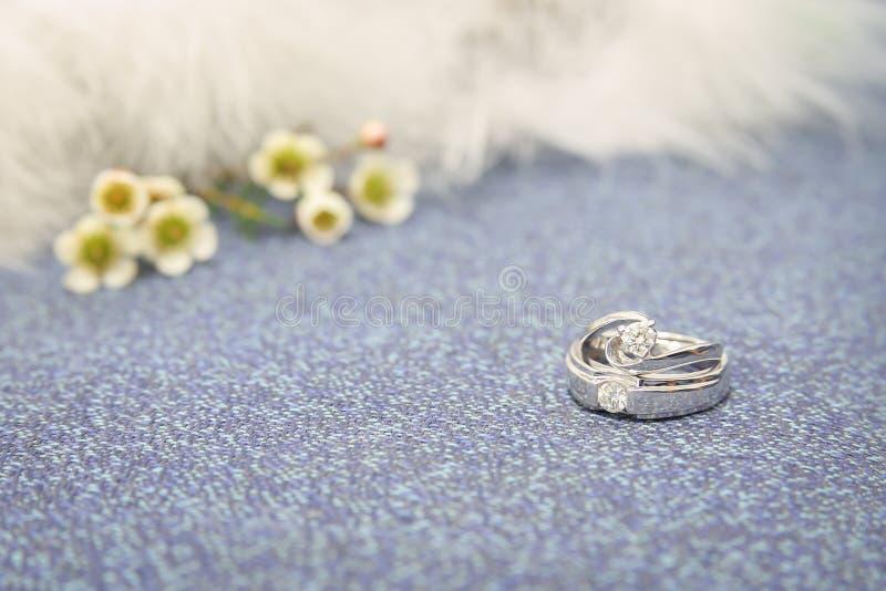 Обручальные кольца на роскошной софе с красивыми цветками стоковая фотография