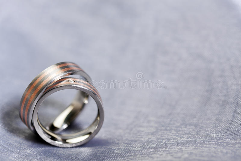 Обручальные кольца на серебряной ткани с космосом экземпляра стоковая фотография