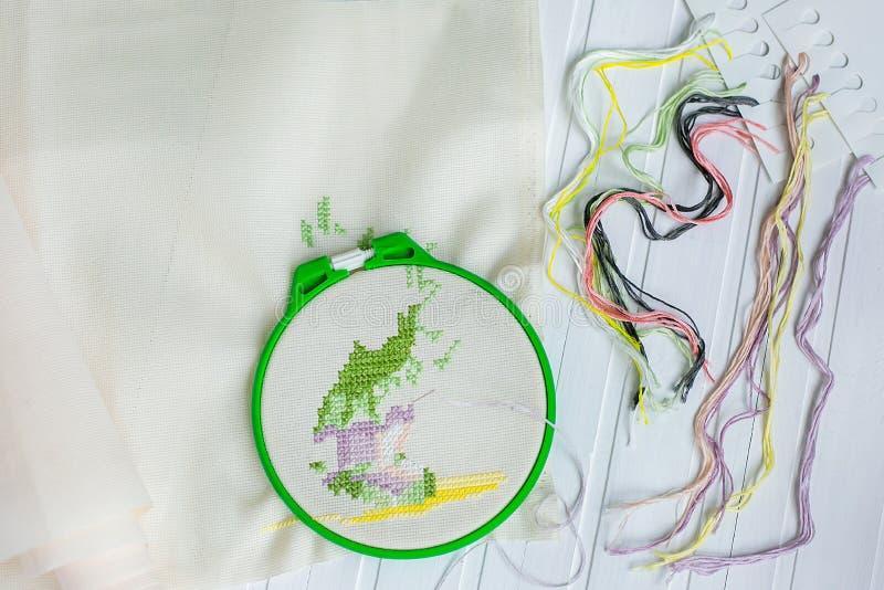 Обруч вышивки с пустой тканью, покрашенными шить потоками и различными шить кнопками стоковая фотография