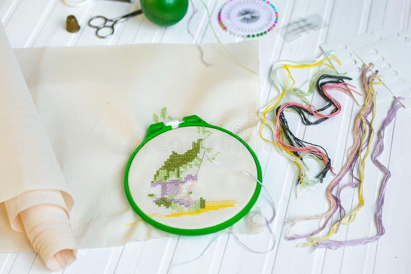 Обруч вышивки с пустой тканью, покрашенными шить потоками и различными шить кнопками стоковое изображение