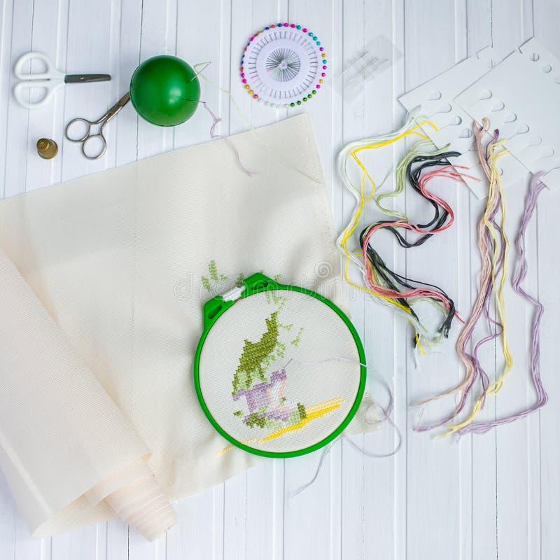 Обруч вышивки с пустой тканью, покрашенными шить потоками и различными шить кнопками стоковая фотография rf