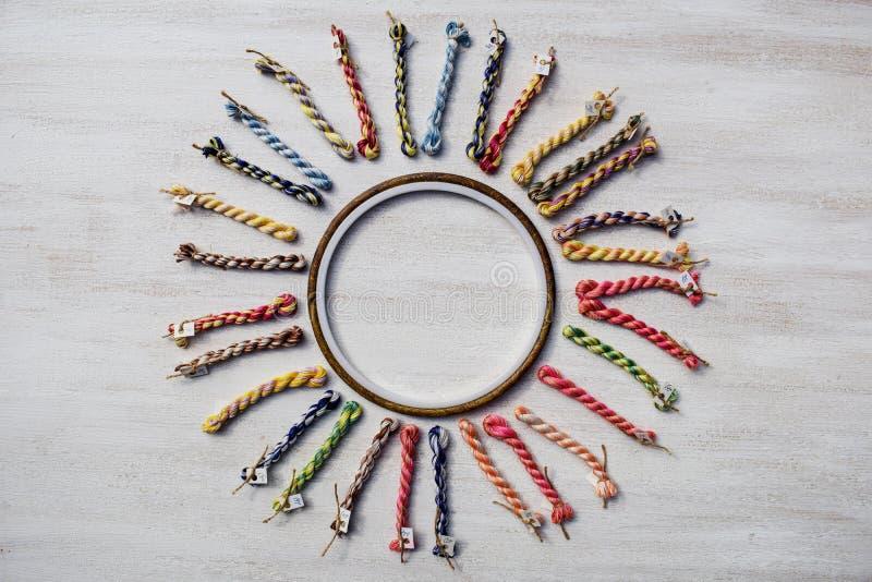 Обруч вышивки с холстом и яркими шить потоками сформированными как солнце стоковое изображение