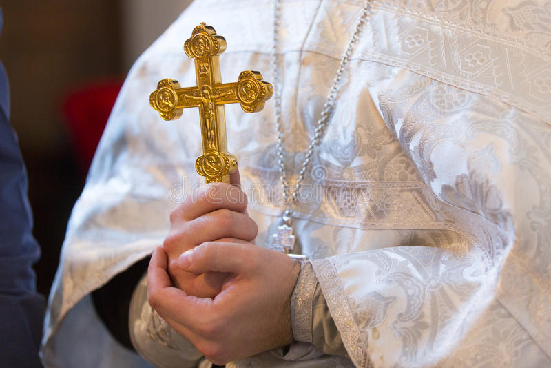 Обряд крещения - золотой крест в правоверных руках священника стоковая фотография