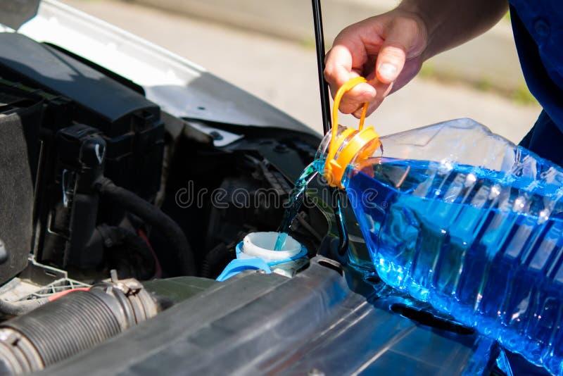 Обслуживайте работника, лейте внутри жидкость шайбы танка для моя окон автомобиля стоковые фото