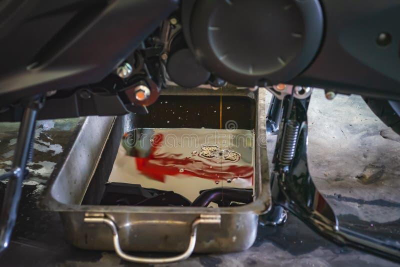 Обслуживание мотоцикла, изменение масла двигателя самоката на гараже стоковая фотография