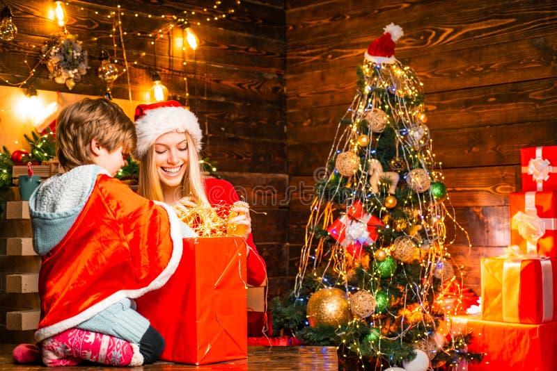 Обслуживание семьи украшая Молодая сестра с мальчиком помогает на установке светов рождества стоковые фотографии rf