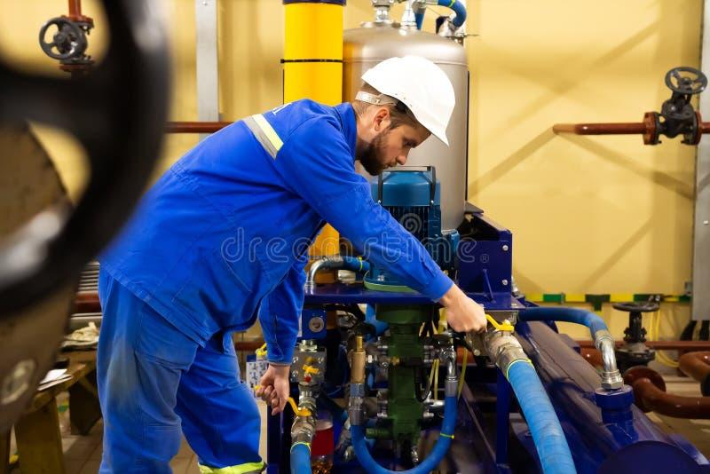 Обслуживание техника промышленного масляного насоса на фабрике стоковые фото