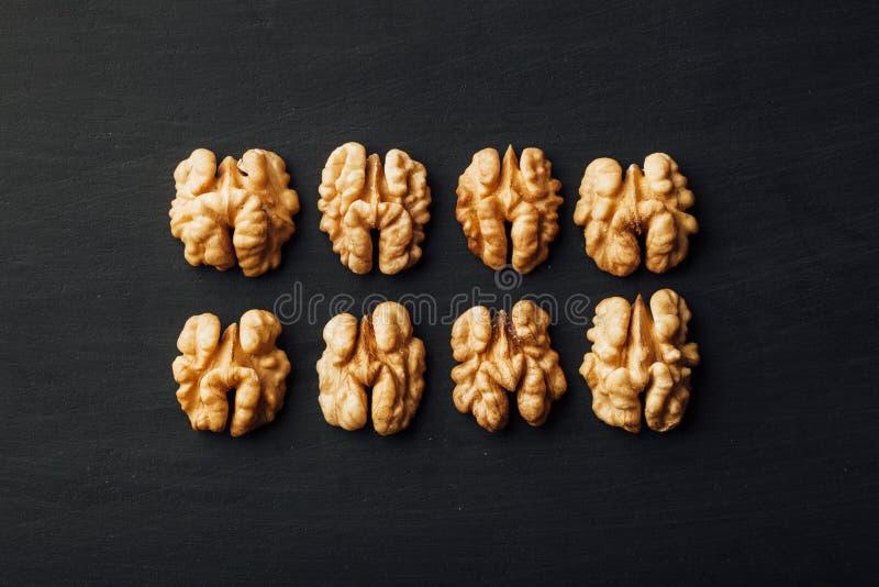 Обстреливаемые грецкие орехи в ряд на черноте стоковые изображения