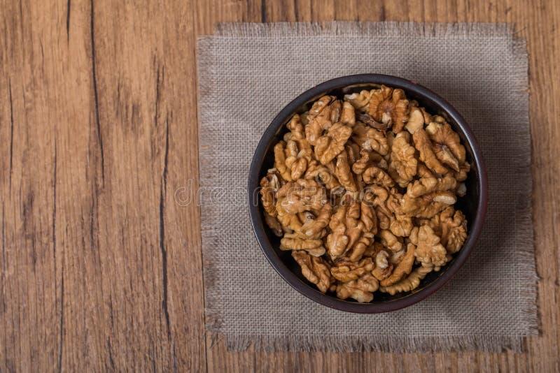 Обстреливаемые грецкие орехи в шаре на деревянной предпосылке стоковая фотография rf