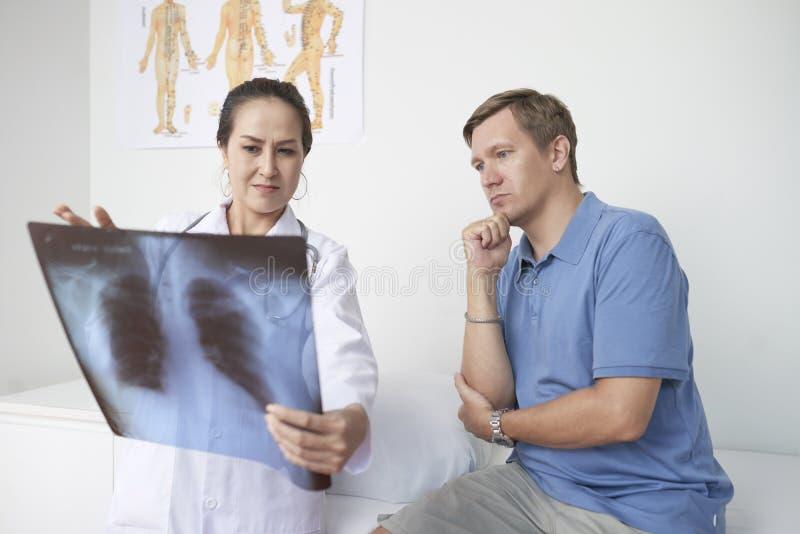 Обсуждать рентгеновский снимок с пациентом стоковые изображения