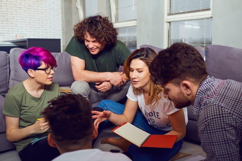 Обсуждают группу в составе молодые люди студентов внутри помещения стоковые изображения