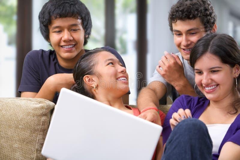 обсуждающ компьтер-книжку что-то подростки стоковое фото