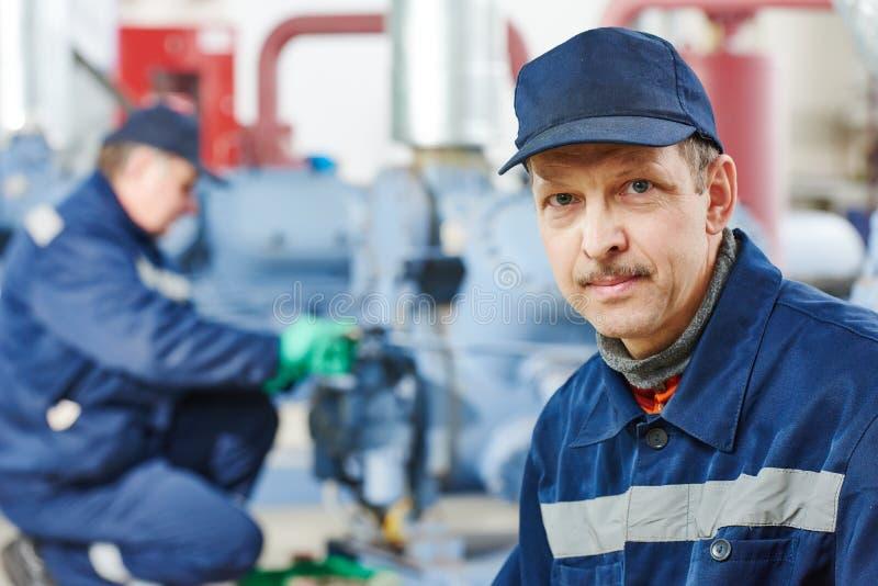 Обслуживайте работника на промышленной станции компрессора стоковые фотографии rf