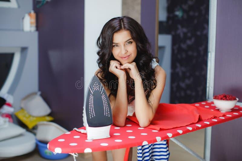 Обслуживания счастливой молодой милой женщины утюжа стоковое изображение