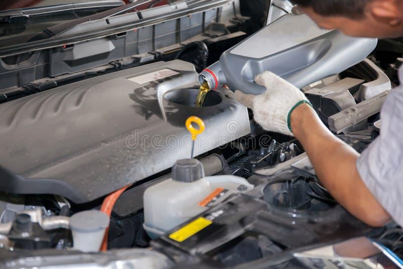 Обслуживая механик лить новую смазку масла в двигатель автомобиля стоковое фото rf