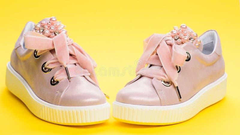Обувь для девушек или женщин украшенных с жемчугом отбортовывает Блестящая концепция обуви Милые ботинки на желтой предпосылке стоковая фотография