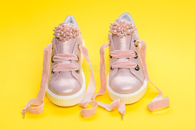 Обувь для девушек или женщин украшенных с жемчугом отбортовывает Милые ботинки на желтой предпосылке Удобная концепция обуви стоковое изображение