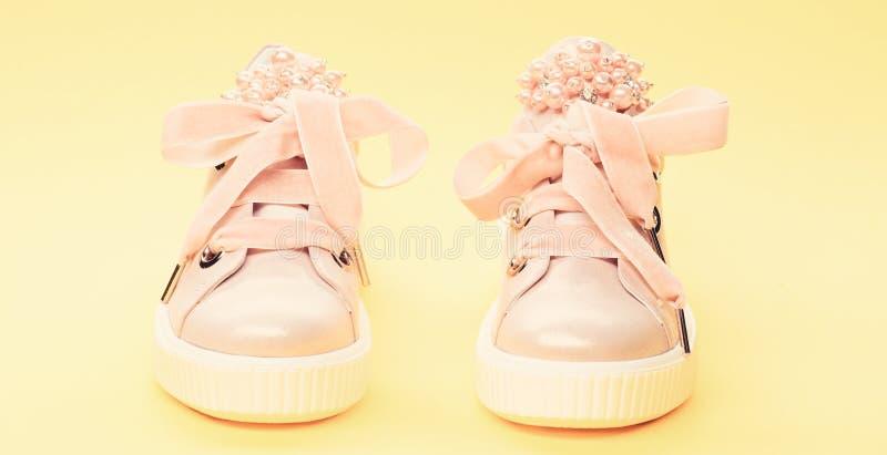Обувь для девушек или женщин украшенных с жемчугом отбортовывает Удобная концепция обуви Милые ботинки на желтой предпосылке стоковое изображение rf