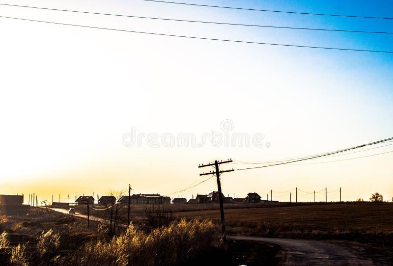 Обширные пространства обширной страны Дорога надземная передающая линия скачет небо, начало расцвета природы farmhouses стоковые фото