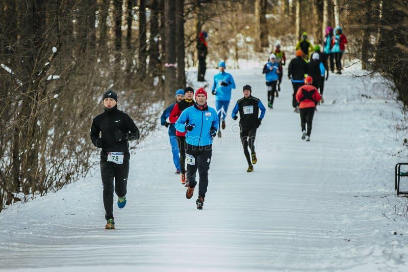 Общая программа бежать через снежную группу в составе переулка парка спортсмены людей стоковые фотографии rf