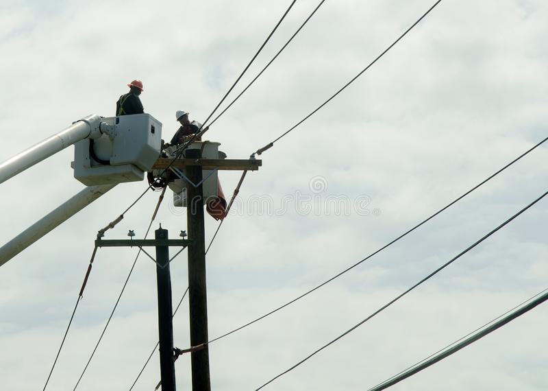 Общего назначения работники ремонтируя кабели от автотелескопической вышки стоковая фотография rf