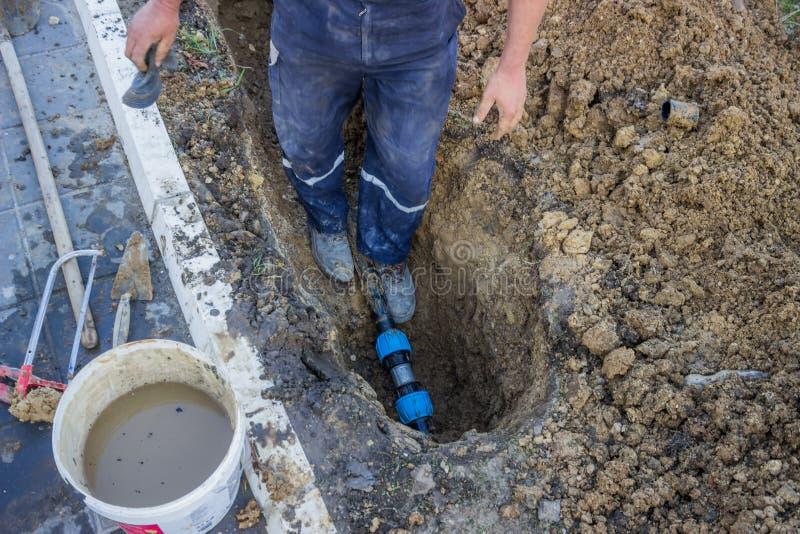 Общего назначения работник в ремонте канавы сломанная труба 3 стоковое фото