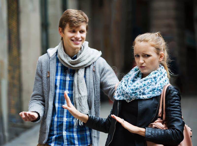 Общественное домогательство: человек гоня раздражанную девушку стоковые изображения