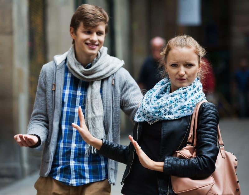 Общественное домогательство: человек гоня раздражанную девушку стоковые фотографии rf
