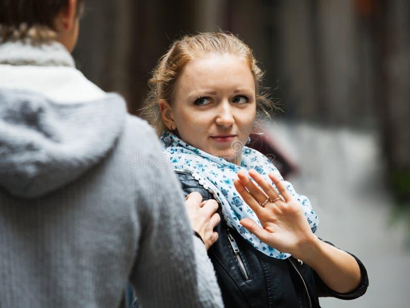 Общественное домогательство: человек гоня раздражанную девушку стоковая фотография rf