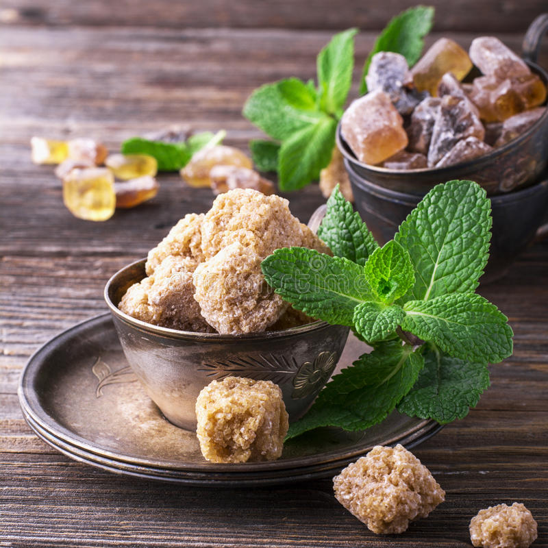 Объединяйте коричневый тростниковый сахар в блюдах металла года сбора винограда с sprig свежей мяты на простой деревянной предпос стоковое изображение rf