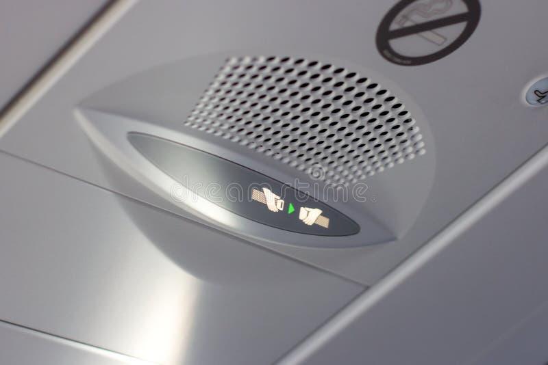 Объявление внимания для пассажиров прикрепляет ваш знак ремня безопасности на доске информации внутри кабины самолета стоковые фото
