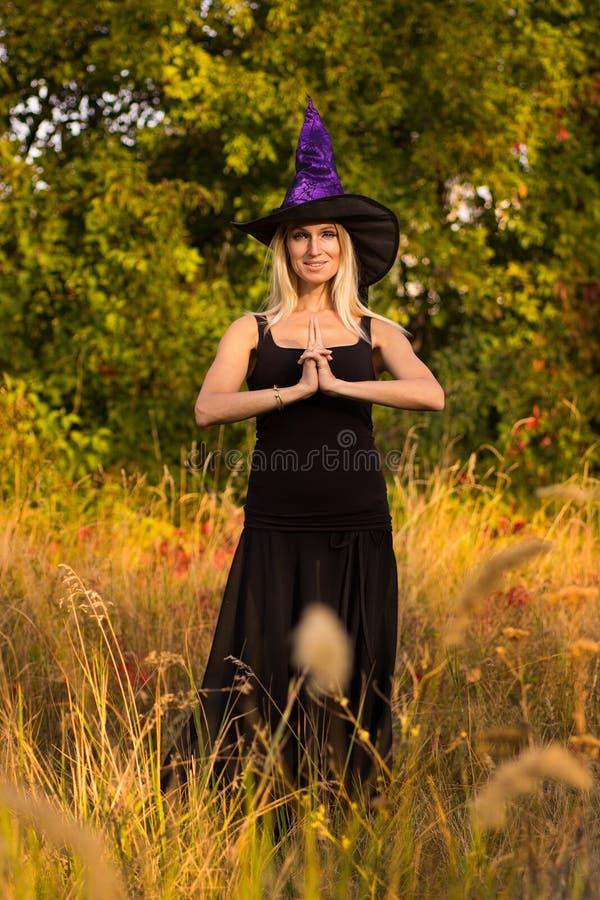 Обычная женщина в йоге костюма ведьмы практикуя стоковые фото