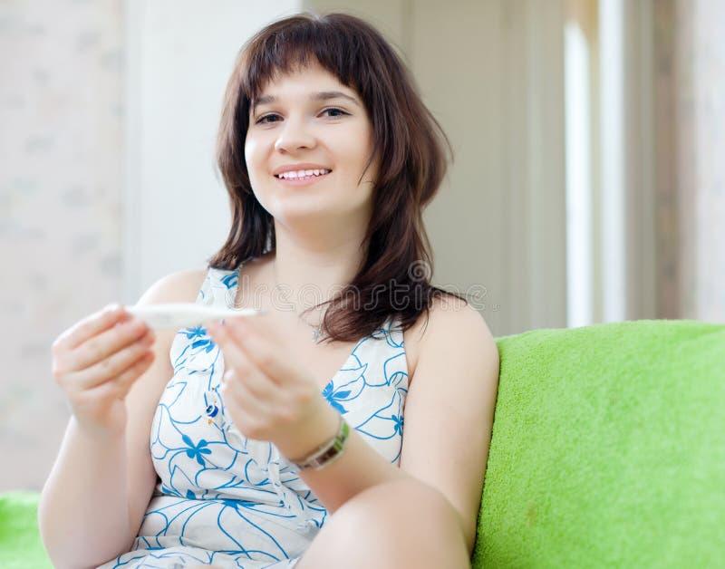 Обычная женщина на софе с термометром стоковые изображения