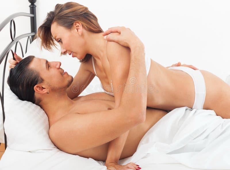 Обычные любовники целуя в кровати стоковые фотографии rf