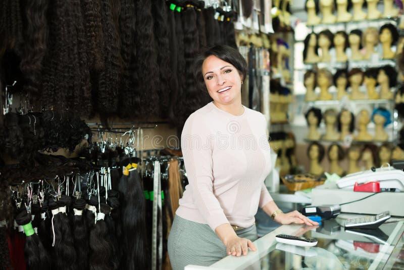 Обычный женский ассистент продавая естественные парики стоковое изображение