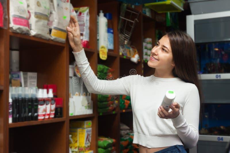 Обычный молодой женский клиент покупая сухую еду для любимчиков в магазине стоковые изображения rf