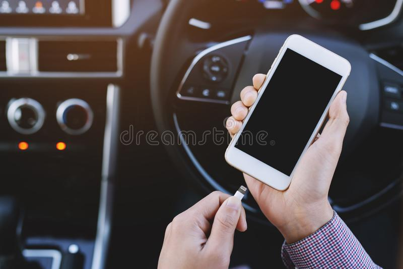 обязанность удерживания руки телефон батареи в автомобиле стоковое фото