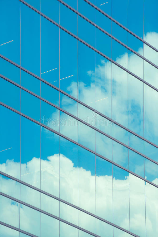 Облака отраженные в современном окне здания стоковые изображения