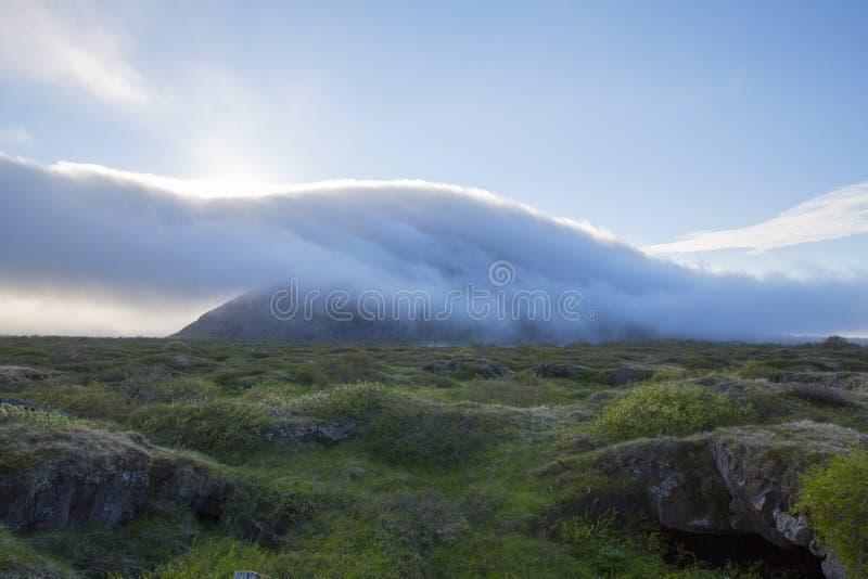 Облака причаливая от горы стоковые изображения